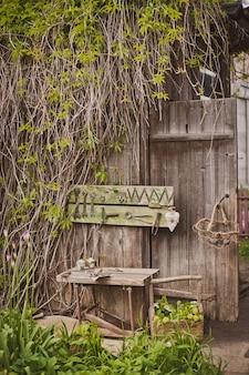 Ontwerp van de fotozone in een rustieke stijl, oude houten deuren en planken met gereedschap en lentebloemen.