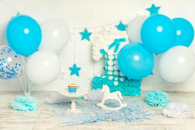 Ontwerp van de fotozone voor de verjaardag van een eenjarige jongen in blauw met ballonnen en een cake, het concept van de vakantie en decor