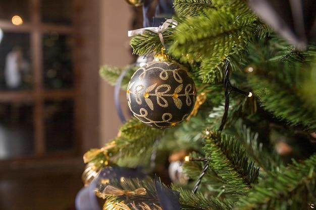 Ontwerp van de kerstboom. trendy kerstboom met gouden en zwarte ballen. nieuwjaar, kerstmis concept