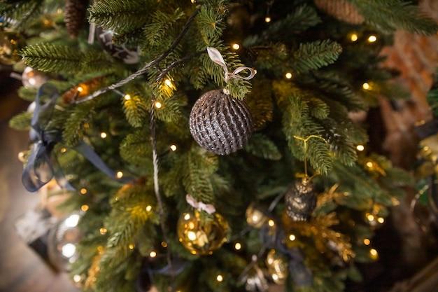 Ontwerp van de kerstboom. trendy kerstboom met gouden en zwarte ballen. nieuwjaar, kerstmis concept Premium Foto