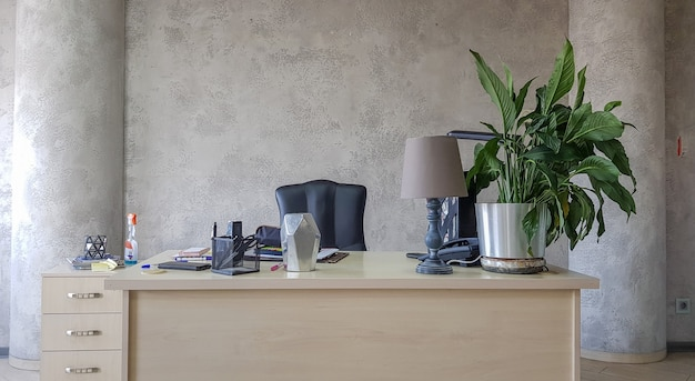 Ontwerp van een werkplek op kantoor met moderne apparatuur en voorzieningen op een grijze muurachtergrond.