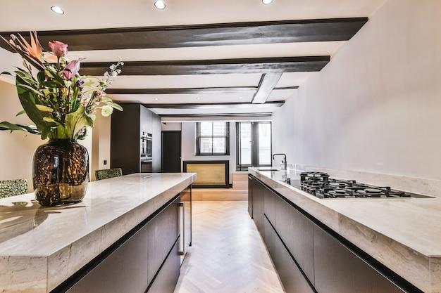 Ontwerp van open keuken met stenen werkbladen en eiland in het midden onder het plafond met houten balken