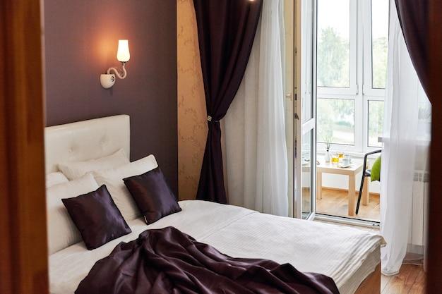 Ontwerp van slaapkamer, in bruine en witte tinten, met balkon, groot wit bed