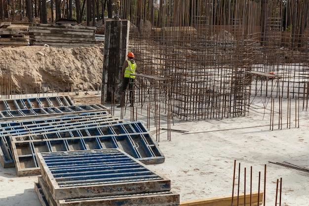 Ontwerp van wapeningskooi van wapening voor betonnen framehuis, bakstenen huis, bekisting voor betonstorten, bouwplaats, werkende kraan, bouw van huizen