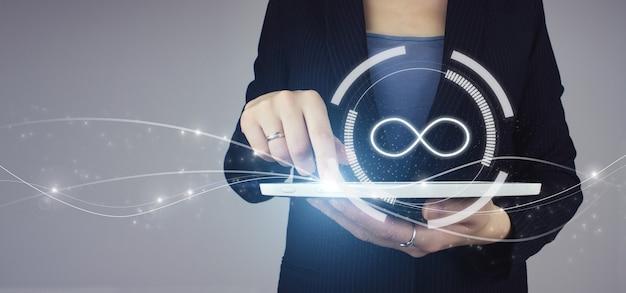 Ontwerp voor hergebruik en hernieuwbare materiaalbronnen. witte tablet in zakenvrouw hand met digitale hologram oneindigheidssymbool op grijze achtergrond. de oneindige weg naar nergens, zakelijk verwarringsconcept.