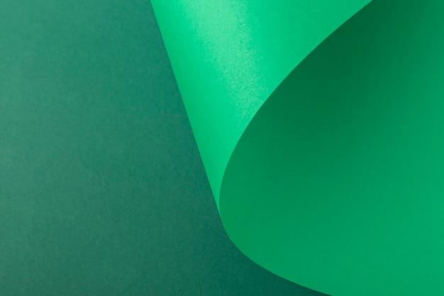 Ontwerpachtergrond van gevouwen krul van groen karton. bovenaanzicht, plat gelegd.