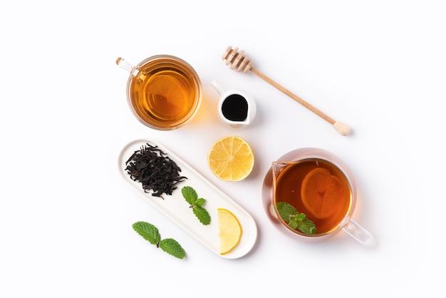 Ontwerpconcept bovenaanzicht van honing zwarte thee met gele citroen en muntblad op witte tafel achtergrond.
