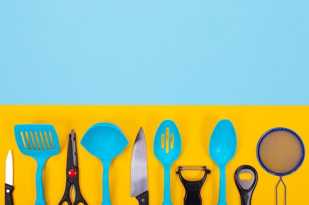 Ontwerpconcept keukengerei met copyspace op blauw-gele achtergrond wordt geïsoleerd die
