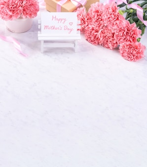 Ontwerpconcept - mooie bos anjers op marmeren witte achtergrond, bovenaanzicht, kopie ruimte, close-up. moederdag cadeau idee inspiratie.