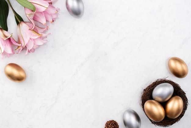 Ontwerpconcept van gouden en zilveren paaseieren in het nest met roze leliebloem op heldere marmeren witte lijstachtergrond.