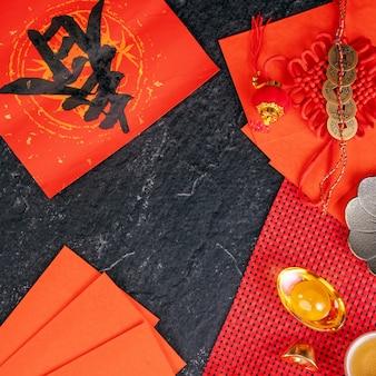 Ontwerpconcept van het chinese nieuwe maanjaar januari - feestelijke accessoires, rode enveloppen (ang pow, hong bao), bovenaanzicht, plat leggen, overhead hierboven. het woord 'chun' betekent komende lente.