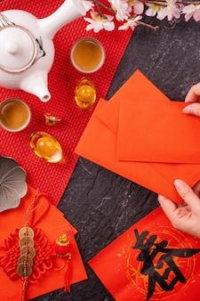 Ontwerpconcept van het chinese nieuwe maanjaar januari - vrouw die rode enveloppen geeft (ang pow, hong bao) voor geluksgeld, bovenaanzicht, plat, overhead hierboven. het woord 'chun' betekent komende lente.