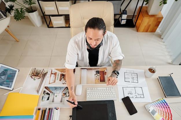 Ontwerper bezig met grafisch tablet bij het maken van 3d-schets van interieurontwerp voor klant