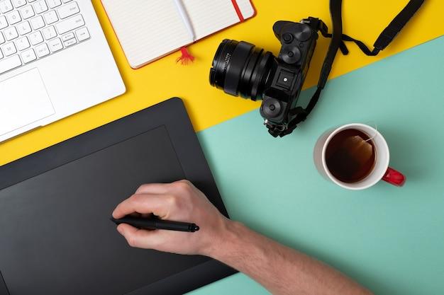 Ontwerper die grafische tablet gebruikt bij digitaal werk en fotobewerking