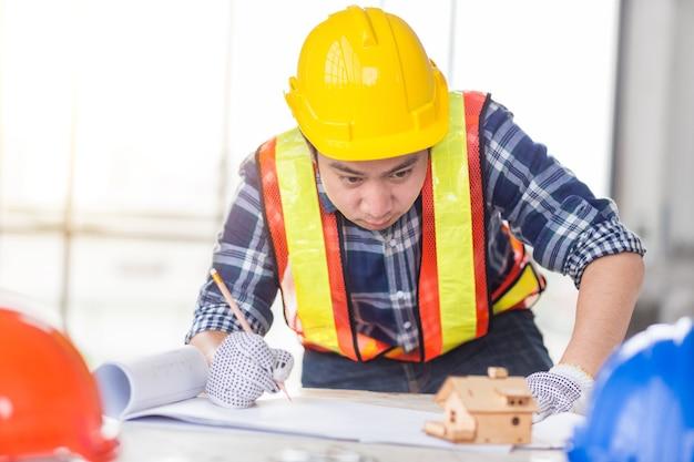 Ontwerper en mannelijke burgerlijk ingenieur ontwerpen een idee voor huis- en industrieel bouwproject in bedrijfsbureau