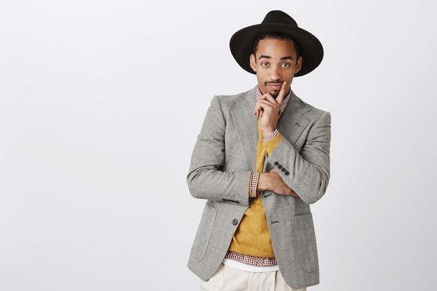 Ontwerper kijkt naar model in zijn kleren. portret van stijlvolle knappe jongeman in stijlvolle formele outfit en hoed, hand op kin, nieuwsgierig staren, geïnteresseerd in discussie