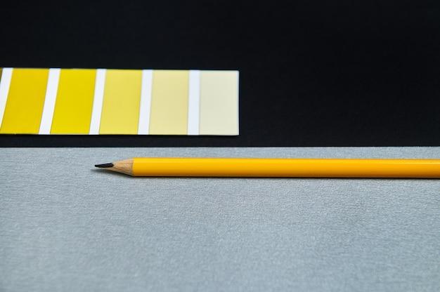 Ontwerper kleurstalen en houten potlood op zwarte achtergrond. verloop van geel op het kleurenwiel.