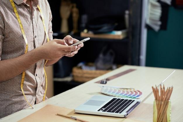 Ontwerper met behulp van smartphone op het werk