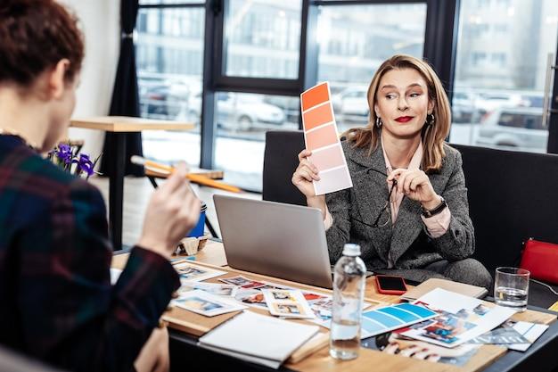 Ontwerper met blond haar. blondharige ontwerper met rode lippen in gesprek met persoonlijke assistent tijdens het kiezen van kleuren
