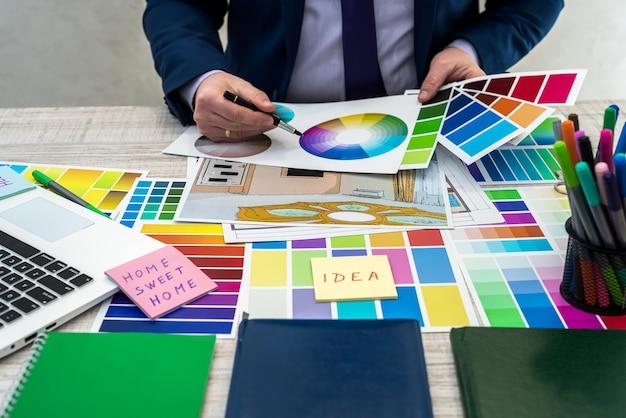 Ontwerper ontwikkelt een schets van interieurillustratie met kleurenschema van materiaal op een tafel, kantoorwerkplek. desktop van een architect en interieurontwerper met voorbeelden van apparatuur en materialen