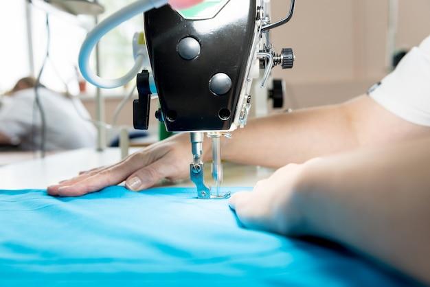 Ontwerper op maat naai de jurk. de naaimachine van het vrouwengebruik voor zijn werk.