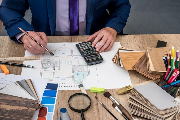 Ontwerper tekent een huisontwerp met een keuze uit houten modellen.