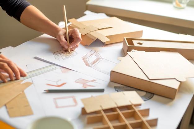 Ontwerper tekent een mockup voor het vervaardigen van een kartonnen doos.
