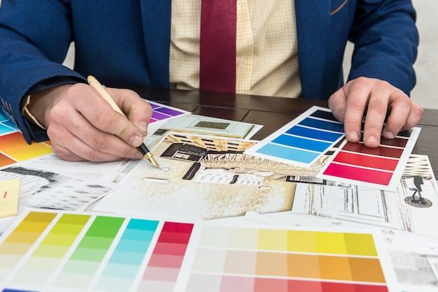 Ontwerper werk op kantoor met creatieve schets en kleurstaal voor moderne renovatie. architect project