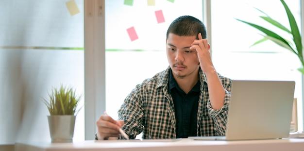 Ontwerper werkt aan zijn project en ziet er stressvol uit
