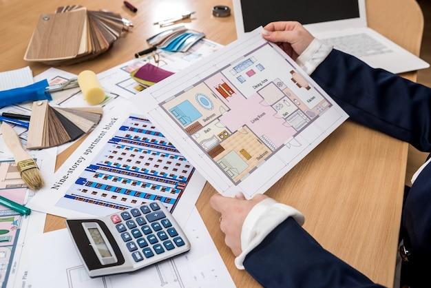 Ontwerper werkt op kantoor met kleurstalen, een laptop en een plattegrond van het gebouw