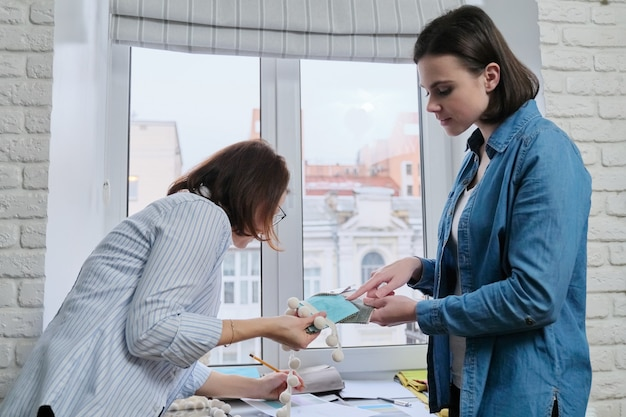 Ontwerpers die stoffen en accessoires voor gordijnen kiezen met behulp van paletten met monsters