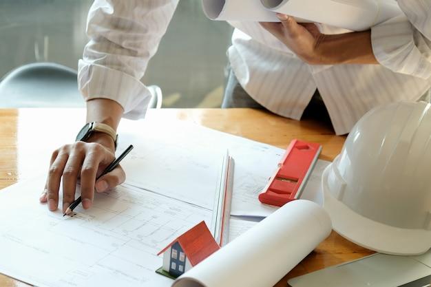 Ontwerpers ontwerpen huizen. model huizen en huisplannen op tafel.
