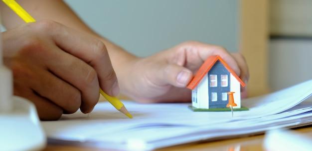 Ontwerpers ontwerpen huizen. modelhuizen worden in de hand gehouden.