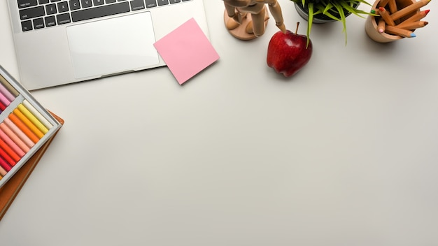 Ontwerperwerkruimte met verfgereedschap, laptop, appel en kopieerruimte, bovenaanzicht, creatieve mock-upscène
