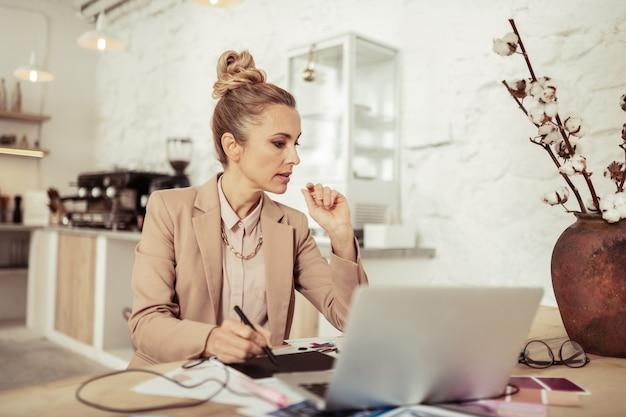Ontwerpproces. doordachte mooie vrouw tekenen schetsen van nieuwe jurken zittend op de laptop.