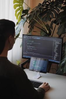 Ontwikkelaar codeert met scherm en tablet freelancer thuis thuiskantoorinrichting met planten