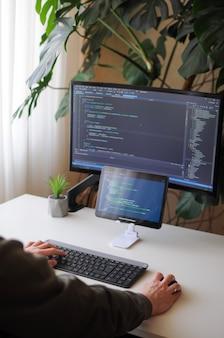 Ontwikkelaar codeert met scherm en tablet freelancer werkt vanuit huis thuiskantoor met plant