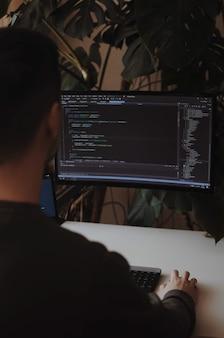 Ontwikkelaar codeert met scherm freelancer werkt vanuit huis thuiskantoor decor met planten