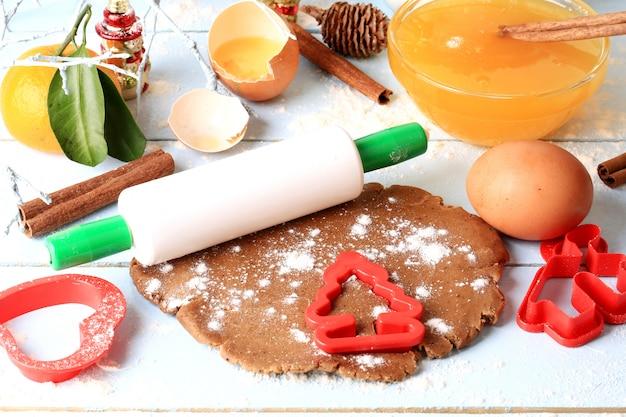 Ontwikkeld deeg voor de eigengemaakte cakes van peperkoekkerstmis op een lichte houten achtergrond selectieve zachte nadruk rustieke stijl