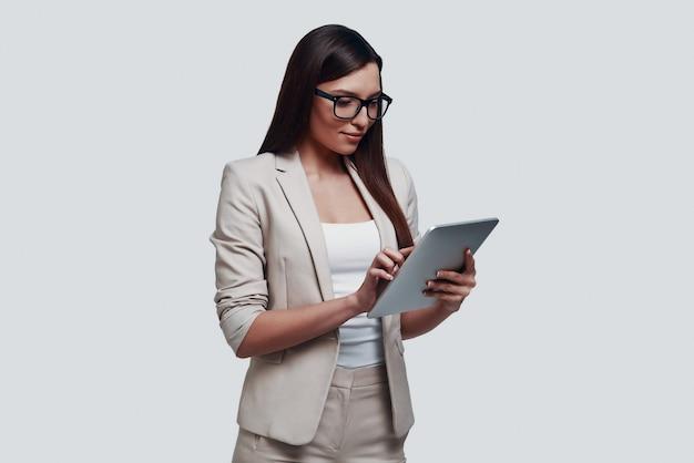 Ontwikkelen van nieuw project. aantrekkelijke jonge vrouw die met behulp van digitale tablet werkt terwijl ze tegen een grijze achtergrond staat