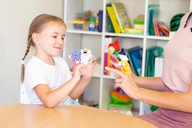 Ontwikkelings- en logopedielessen met een kind-meisje. logopedische oefeningen en vingertheaterspelletjes.