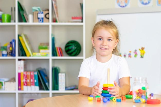 Ontwikkelings- en logopedielessen met een kindmeisje. logopedische oefeningen en spelletjes met een gekleurde piramide