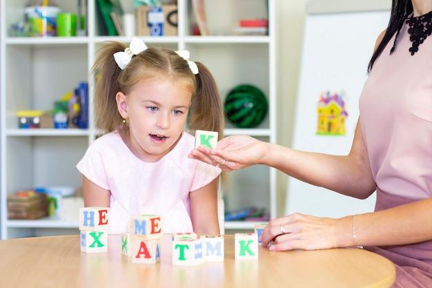 Ontwikkelings- en logopedische lessen met een kind-meisje. logopedie-oefeningen en spelletjes met letters. dobbelsteenspel