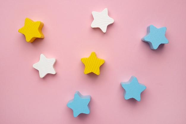 Ontwikkelingsspeelgoed voor kinderen voor de ontwikkeling van motorische vaardigheden een halve maan houten sterrenbalancer op een roze achtergrond