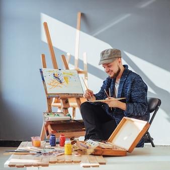 Ontworpen door kunstenaar man afwerking zijn meesterwerk houdt een borstel in de hand.