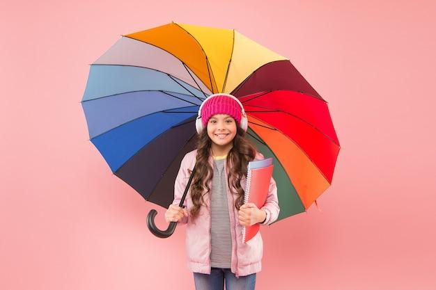 Ontworpen voor regenachtig weer. weinig schoolmeisje houdt kleurrijke paraplu op roze achtergrond. klein kind terug naar school in de herfst. schattig kind in oortelefoons gaat op regenachtige dag naar school. de beste leerschool.
