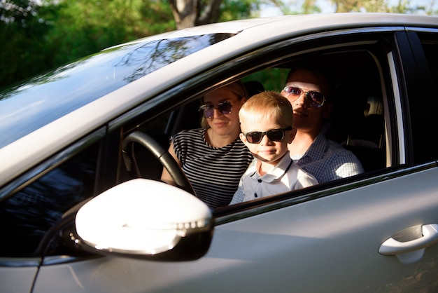 Onveilig rijden. een klein kind zit in de armen van haar moeder op de bestuurdersstoel.