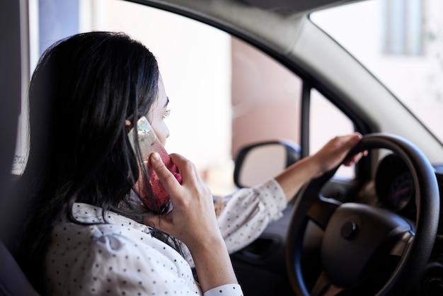 Onveilig rijden jonge multiraciale vrouw praten aan de telefoon tijdens het rijden afgeleid rijdende vrouw