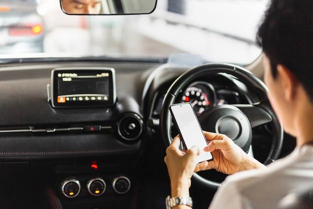 Onverantwoordelijke man die smartphone gebruikt tijdens het rijden