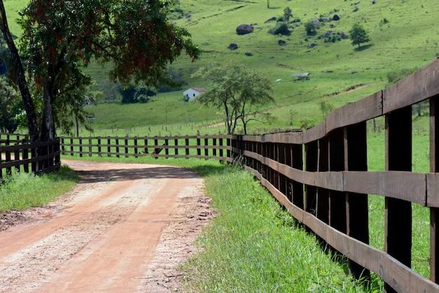 Onverharde weg geflankeerd door een donkere houten omheining, met bomen en gras. brazilië platteland
